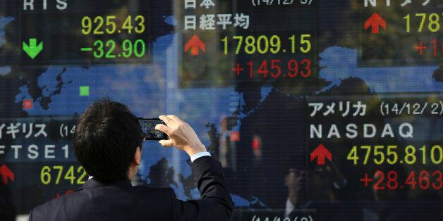 A man photographs an electronic stock board of a securities firm  in Tokyo, Wednesday, Dec. 3, 2014. Japanese and Chinese sha