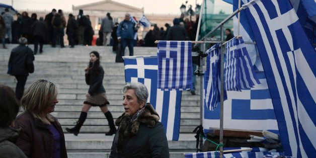 Women talk next to Greek flags for sale in Syntagma square, Monday, Feb. 16, 2015. Greece and its creditors in the 19-country