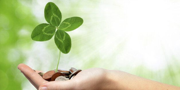 woman's hand are holding a money with clover on green background