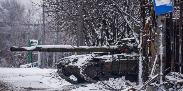 A pro-Russian rebels' tank stands behind a destroyed bus stop near Donetsk airport, Eastern Ukraine, Tuesday, Jan. 6, 2015. U