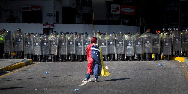 A demonstrator wearing a Venezuelan flag stands in front of police dressed in riot gear during a protest in Caracas, Venezuel