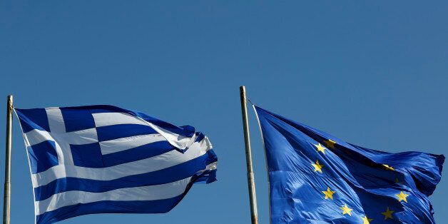 A Greek national flag, left, flies alongside a European Union (EU) flag in Athens, Greece, on Thursday, Feb. 19, 2015. German