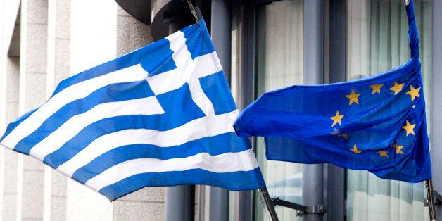 The Greek, left, and EU flag flap in the wind outside the Greek embassy in Brussels on Friday, Feb. 20, 2015. Eurozone financ