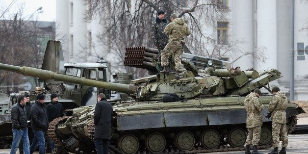 KIEV, UKRAINE - FEBRUARY 22:  Security forces inspect a heavy tank and a rocket launcher truck that are part of an exhibition