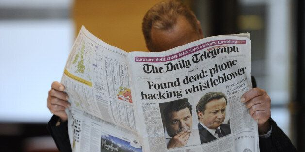 A person reads on July 19, 2011, in Paris, the British daily newspaper, The Daily Telegraph of which front page is on the spi