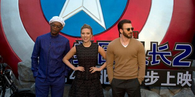 Actress Scarlett Johansson stands next to Samuel L. Jackson, left and Chris Evans at right during a publicity event ahead of