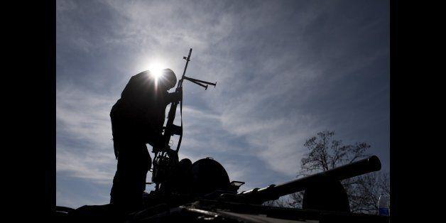 A Ukrainian soldier stands atop a military vehicle near Artemivsk, eastern Ukraine, Monday, Feb. 23, 2015. Ukraine delayed a