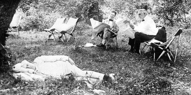 Thomas A. Edison sleeps, while President Warren Harding and tire magnate Harvey Firestone read newspaper in 1921. (AP Photo)