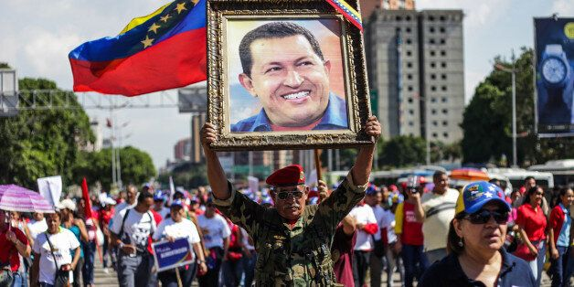 CARACAS, VENEZUELA - DECEMBER 15 :   A man holds a portrait of late Venezuelan leader Hugo Chavez as Venezuelans gather on th