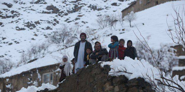 Afghan villagers look on in a village close to an avalanche site in Panjshir province north of Kabul, Afghanistan, Wednesday,