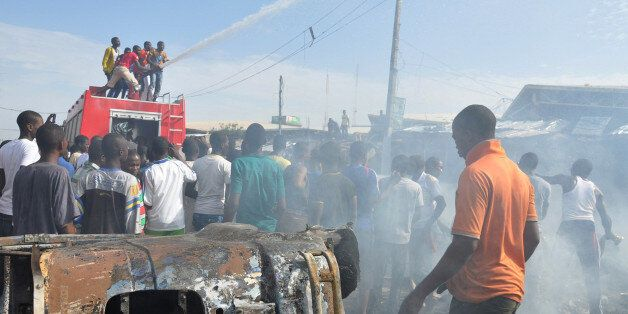 FILE - In this Tuesday, July , 2014 file photo, People gather at the scene of a car bomb explosion, at the central market, in