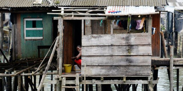 BUENAVENTURA, COLOMBIA - JANUARY 13, 2015: A woman busy with her house duties looks at the camera from the opposite neighborh