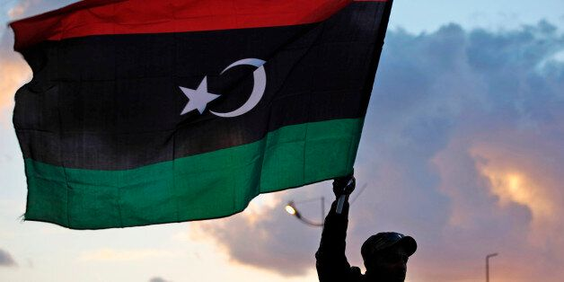 A Libyan waves the national flag during commemorations to mark the second anniversary of the revolution that ousted Moammar G