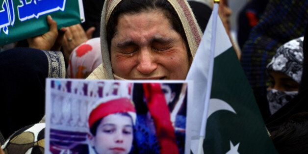 A mother weeps as she carries a picture of her slain son during a tribute to students who were killed in an attack on a schoo