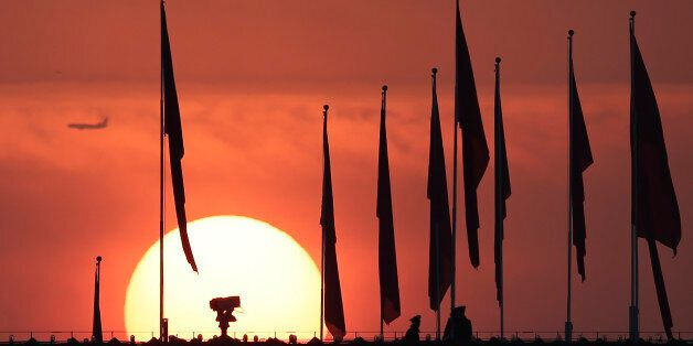 Chinese military personnel watch over Tiananmen Square from a rooftop across from the Great Hall of the People, as the sun ri