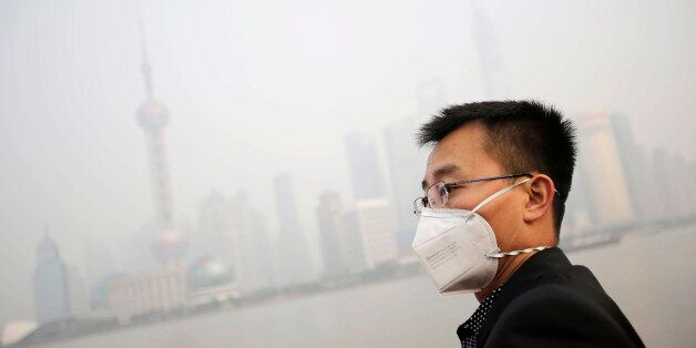 A tourist wearing a protective mask looks at buildings at the Bund under heavy haze in Shanghai, China, Friday, Dec. 20, 2013