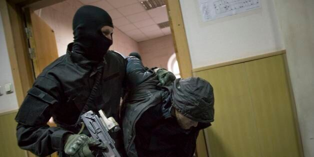 Police escort a man believed to be one of five suspects in the killing of Boris Nemtsov in a court room in Moscow, Russia, Su