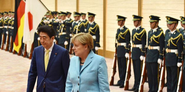 German Chancellor Angela Merkel, second from left, accompanied by Japanese Prime Minister Shinzo Abe, reviews a guard of hono