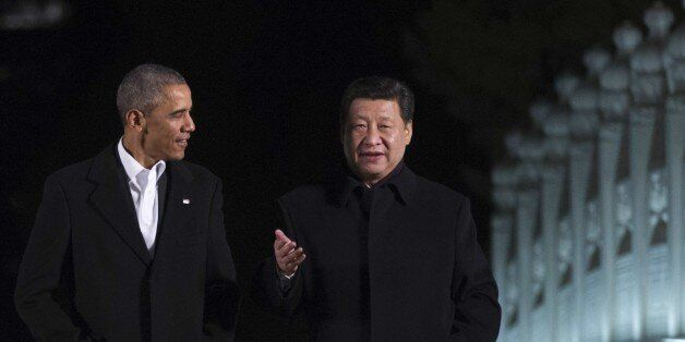 US President Barack Obama (L) walks with China's President Xi Jinping at the Zongnanhai leaders compound, ahead of a dinner i