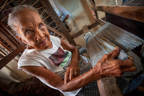 A woman working on her wooden weaving loom in the countryside of Bhutan. (Andrew Eio/Getty Images)