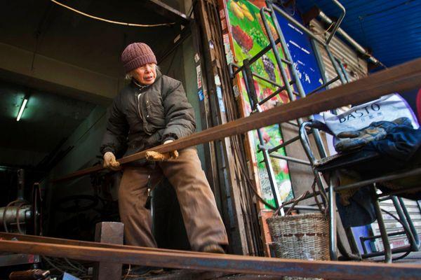 Liu Shujian, a 90-year-old lady, continues her electro welding work at Wanshousi Street on Dec. 5, 2014 in Shenyang, Liaoning