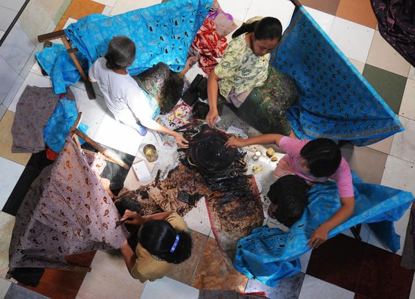Batik craftswomen apply melted wax to fine cotton textiles to produce characteristic figurative designs at a workshop in Solo