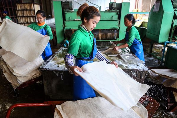 Workers handle rubber sheets as they pass through a rubber sheet washing machine at the Thai Hua Rubber Pcl factory in Samnuk