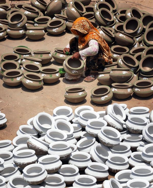 A Pakistani woman potter gives the final touches to earthen pots at a workshop on the outskirts of Lahore on June 9, 2011. (A