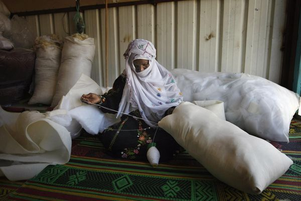 Bedouin shop owner, Farawna Nasra Abu Adjin, 50, fashions a pillow by hand in her workshop started with a micro-finance loan