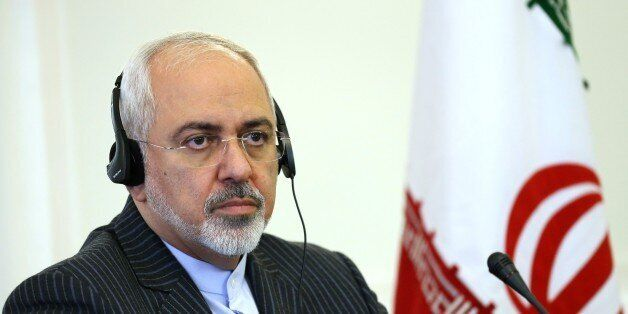Iranian Foreign Minister Mohammad Javad Zarif listens to the translation of a question at a press conference with his Italian