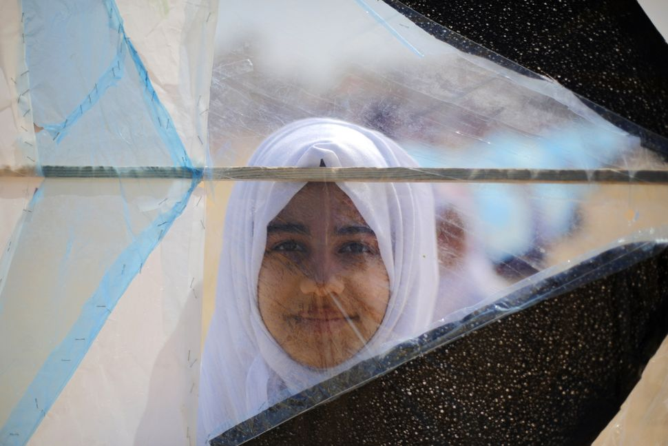 A Palestinian school girl looks through a kite during a gathering to show solidarity with Japan in Khan Younis, Gaza on March