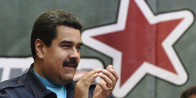 Venezuelan President Nicolas Maduro applauds during a ceremony commemorating the second anniversary of former Venezuelan pres