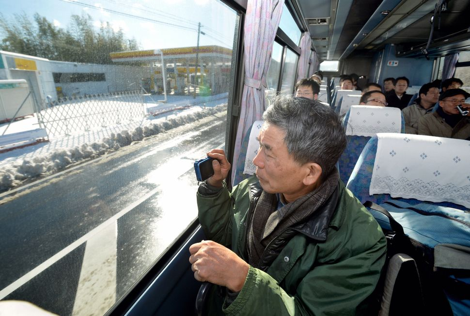 "A passenger snaps a photo of the ""difficult-to-return zone"" from a bus that started operations through the evacuation area on"