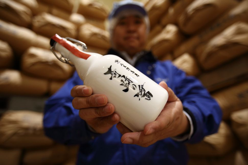"Michihiro Kono, president of Yagisawa Shouten Co., holds a bottle of the company's ""Miracle Soy Sauce"" at its factory in Ichi"
