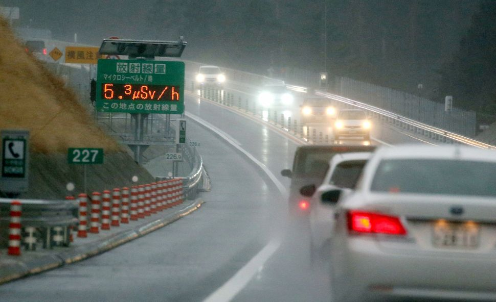 A sign displaying radiation levels is placed at the Joban Expressway on March 1, 2015, in Futaba, Fukushima, Japan. Local gov