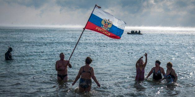 Crimean people wave a Russian national flag as they prepare to swim celebrating an Orthodox Christamas in the Black Sea with