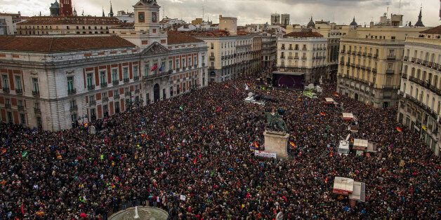 People gather in the main square of Madrid during a Podemos (We Can) party march in Madrid, Spain, Saturday, Jan. 31, 2015. T