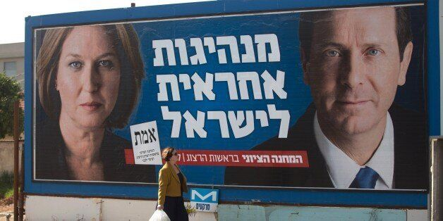 An Israeli woman passes by a campaign poster showing Israeli MP Tzipi Livni (L) and Isaac Herzog co- leaders of the Zionist U