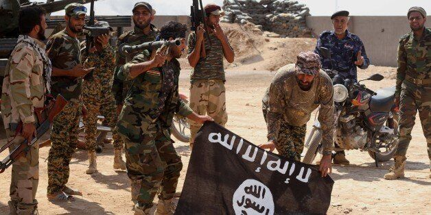 FILE - In this Tuesday, Oct . 7,  2014  file photo, Iraqi security forces hold a flag of the Islamic State group they capture