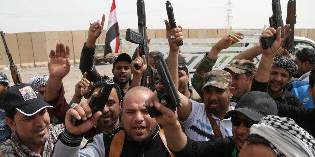 Iraqi Shiite militiamen chant slogans during clashes with the Islamic State group in Tikrit, 130 kilometers (80 miles) north