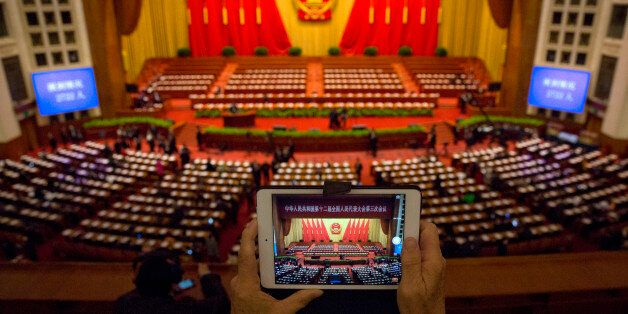 A delegate takes a photo before a plenary session of the National People's Congress in the Great Hall of the People in Beijin