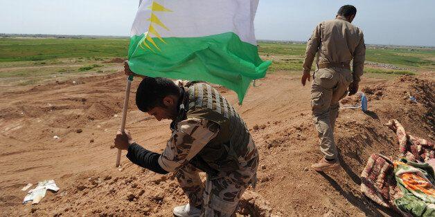 KIRKUK, IRAQ - MARCH 13: A peshmerga fighter plants a Kurdish flag atop a new earth berm position as Iraqi Kurdish forces pus