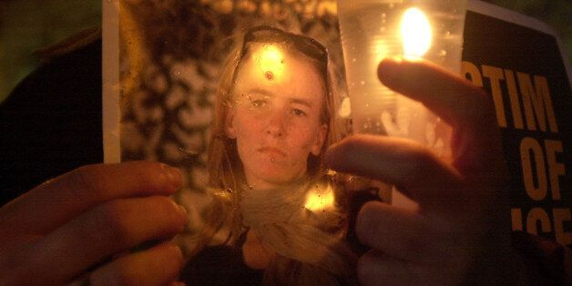 A Palestinian man holds a candle and a picture of American peace activist Rachel Corrie during a memorial service in the West