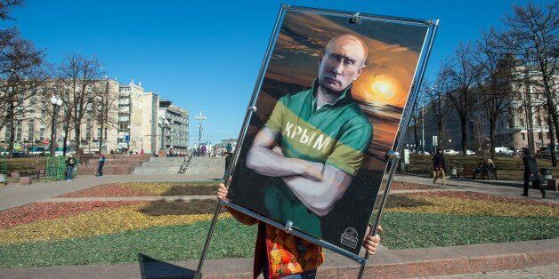 A man carries a picture depicting Russia's President Vladimir Putin in a T-shirt with an inscription reading: 'Crimea' at an