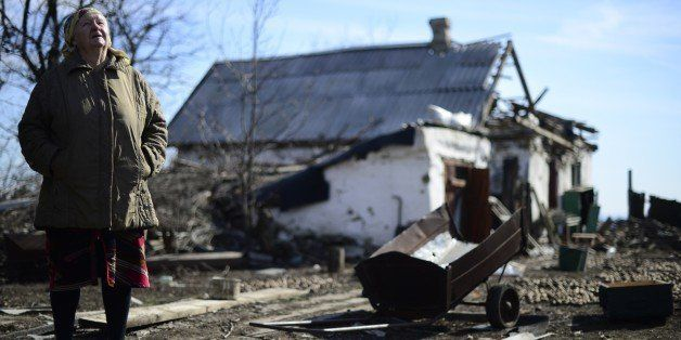 An elderly woman stands close to her damaged house in Nikishyne, south east of Debaltseve March 11, 2015. The town was levell