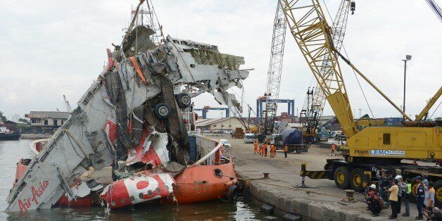 A crane is used to lift the fuselage of the crashed AirAsia QZ8501 plane at the Tanjung Priok port in Jakarta on March 2, 201