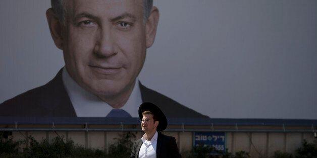 An Orthodox Jewish man walks past a billboard of Israeli Prime Minister Benjamin Netanyahu in Bnei Brak near Tel Aviv, Israel