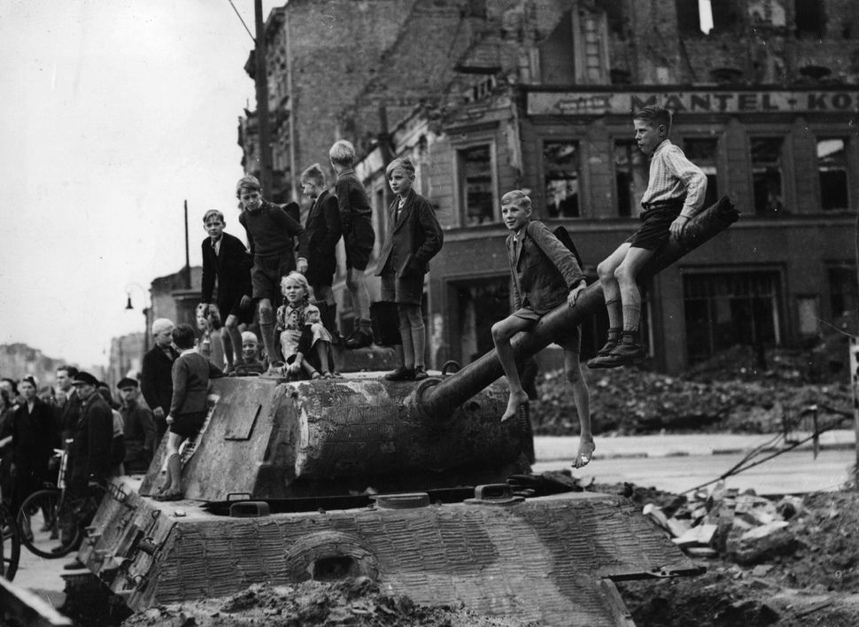 Children play on the bomb sites and wrecked tanks in Berlin, in the aftermath of the fighting in the city in 1945.