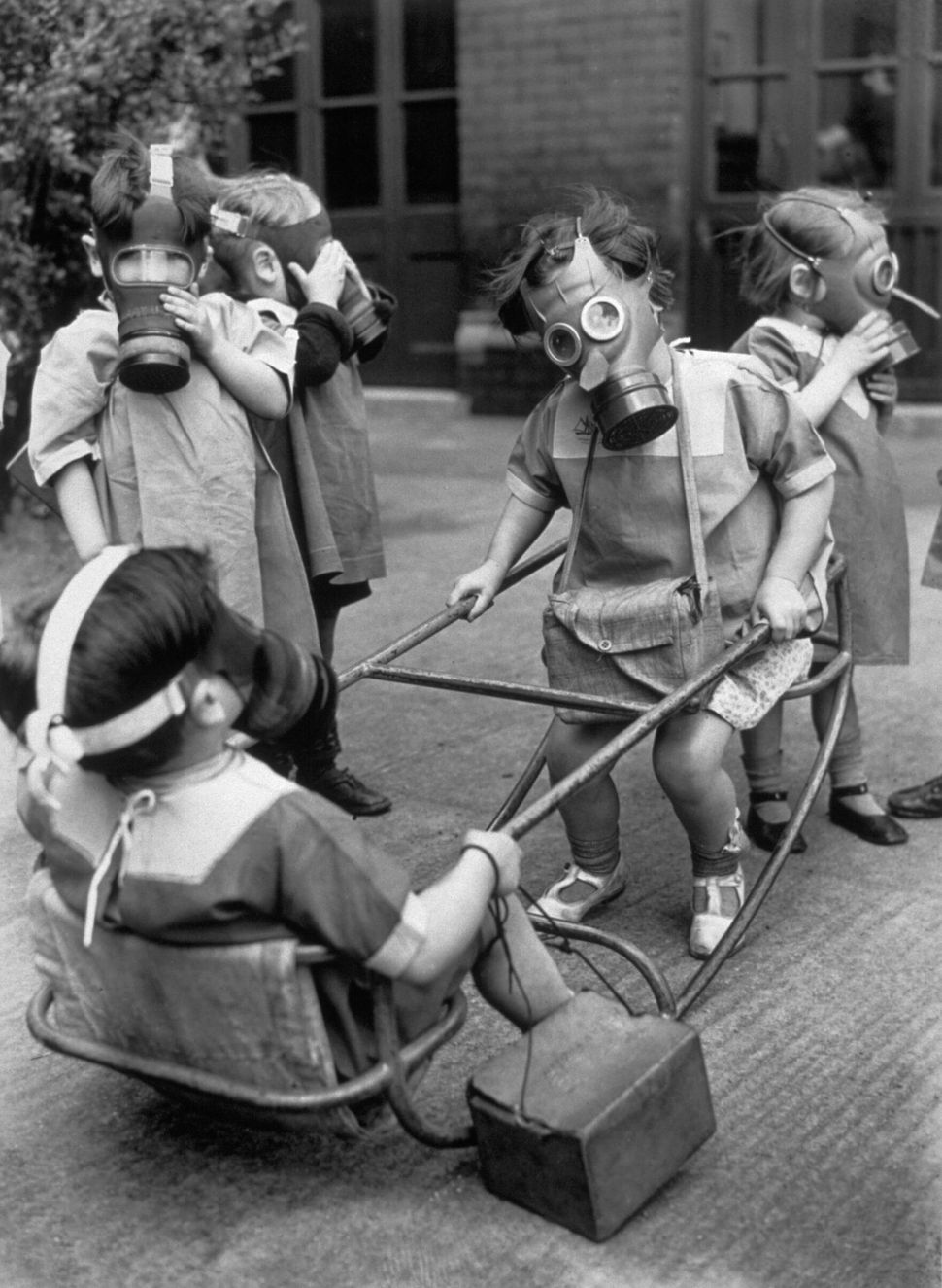 Small children in a playground wearing their gas masks around 1940.