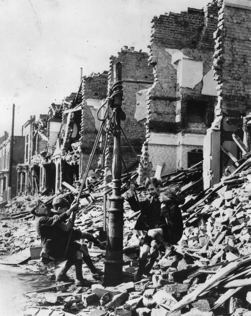 Young boys swinging from a lamp post in the midst of rubble left by a bombing raid on London during the Blitz circa 1940.